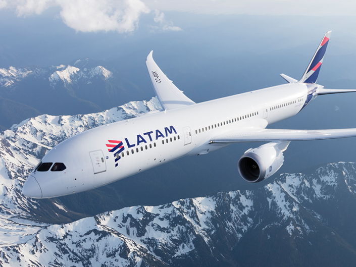 A LATAM Airlines plane flies above snow-capped mountains